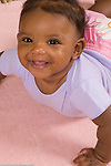 5 month old baby girl portrait on stomach closeup smiling head high vertical