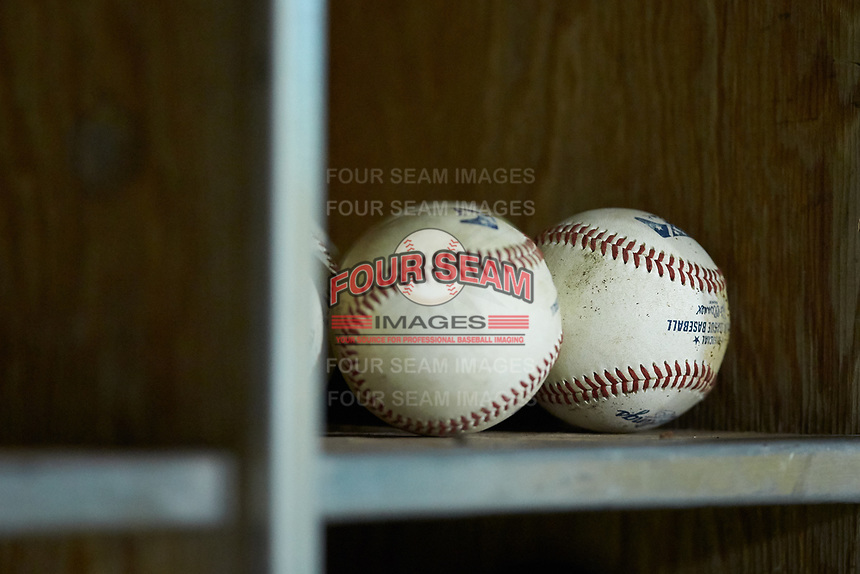 A pair of Midwest League baseballs sit in the helmet rack of the Bowling Green Hot Rods dugout during the game against the Fort Wayne TinCaps at Parkview Field on August 20, 2019 in Fort Wayne, Indiana. The Hot Rods defeated the TinCaps 6-5. (Brian Westerholt/Four Seam Images)