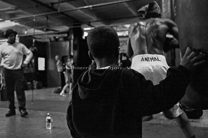A young boy watches Denis Douglin (r), a few years before he turned pro, during a training session at Gleason's Gym in Brooklyn, New York.<br />Photograph by Thierry Gourjon-Bieltvedt. 1995-2005