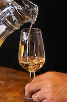 Reinaldo de Lucca pouring a barrel sample of Marsanne white wine from a water pitcher like decanter. Bodega De Lucca Winery, El Colorado, Progreso, Uruguay, South America