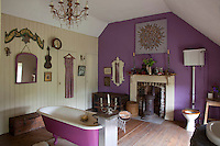 The free standing bath has been painted to match the purple shade on the wall of this bathroom