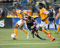 Houston Dynamo midfielder Ricardo Clark (13) retrieves the ball from New England Revolution midfielder Kelyn Rowe (11) as Houston Dynamo midfielder Warren Creavalle (5) moves in to support.  The New England Revolution played to a 1-1 draw against the Houston Dynamo during a Major League Soccer (MLS) match at Gillette Stadium in Foxborough, MA on September 28, 2013.
