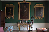 One wall of the restored drawing room is adorned with ancestral portraits in heavy gilt frames