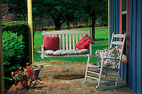 Intimate front porch and entryway into house with swing glider, rocker, and colorful pillows