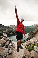 Male hiker playing around for the camera during a break on the climb up Asgard Pass above Colchuck Lake on the way into The Enchantments, Alpine Lakes Wilderness, WA.