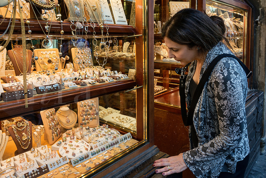 Woman window shopping at one of the many jewelry stores along the Ponte Vecchio bridge, Florence, Italy