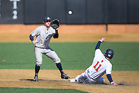 Georgetown Hoyas shortstop Ryan Busch (1) waits for a throw as Greg Wasikowski (11) of the Bucknell Bison slides safely into second base at Wake Forest Baseball Park on February 14, 2015 in Winston-Salem, North Carolina.  The Hoyas defeated the Bison 8-5.  (Brian Westerholt/Four Seam Images)