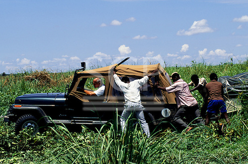 """Chipundu, Zambia. Four wheel drive Jeep and trailer needing a push to escape from the mud """"cross country"""" in a swamp."""