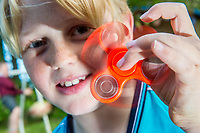A young boy  plays with an orange fidget spinner toy