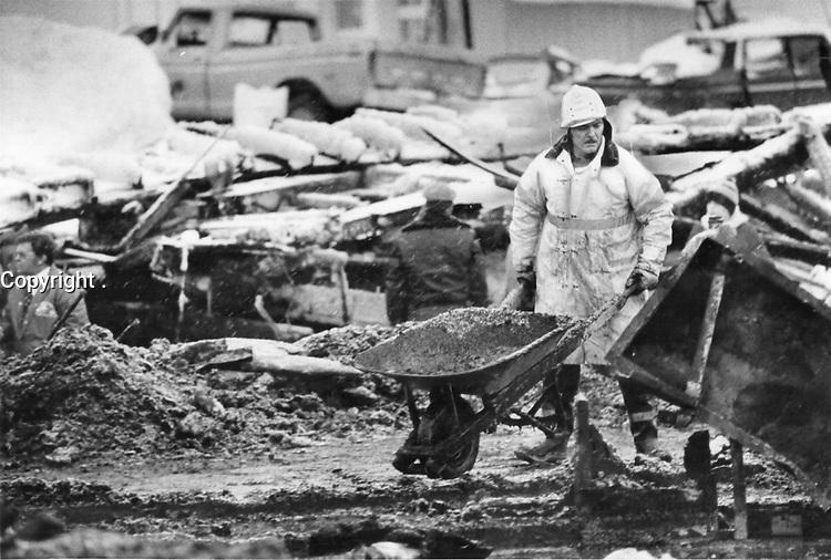 1980 FILE PHOTO - ARCHIVES -<br /> <br /> Les décombres suite a l' Incendie du Jour de l'an,1980, Chapais<br /> <br /> A fire captain wheels out ashes in a search for fire victims.<br />  Jan 1980<br /> <br /> PHOTO : Graham Bezant - Toronto Star Archives - AQP