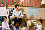 Education preschoool children ages 3-5 female teacher and children in circle time  lesson on the earth and how it is round horizontal