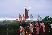 Lolgorian, Kenya. Siria Maasai; woman on the rooftop rejoicing over the rain at the Eunoto coming of a ge ceremony.