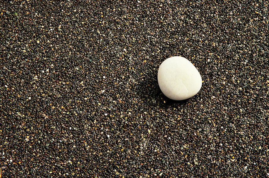 """""""Standing Out in a Crowd""""<br /> Rialto Beach, Washington<br /> 2003<br /> Rialto Beach is one of many beautiful beaches along the Olympic Peninsula near Forks, Washington.  The beach is composed of tiny pebbles smoothed by the tides.  While walking along the beach toward the Hole in the Wall monolith, we picked up driftwood and rocks.  The contrast of the larger oval rock against the small, dark pebbles was stunning, and not unlike the difference between the depressed Indian village of La Push and the town of Forks.  Large sea stacks silhouetted against the calm Pacific Ocean provided outstanding vistas at sunset."""