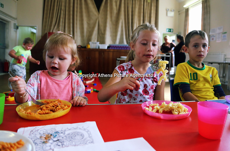 Pictured L-R: Skyla-Mae, 2, Lauren 8 and Ben 6 enjoy hot food at St Teilo Church in Clase, Swansea, UK. Friday 25 August 2017<br /> Re: Free food for children story, Swansea, Wales, UK.