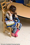 Education preschool 4 year olds emotions sadness separation girl in pretend play dressup outfit holding doll and purse sitting alone covering eyes with arm crying vertical