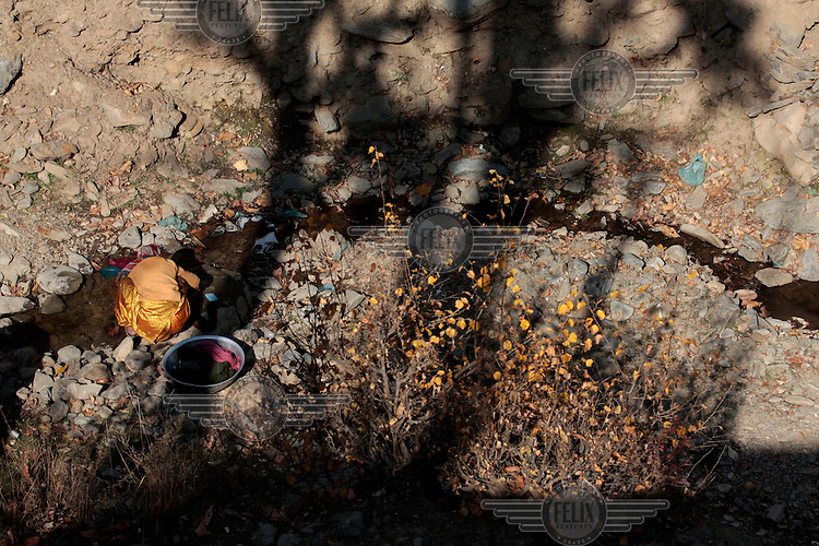 A woman washing clothes in in a small pool of water. A tiny brook is the only source of water near her house. Kashmir, India. © Fredrik Naumann/Felix Features