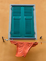 The average clothes dryer in Italy, clothesline and clothespins.  The orange shirt was flapping in the breeze against an orange background.
