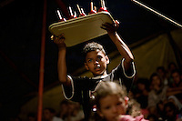 A boy sells toffee apples during an interval at the Sombrillita Circus. When the attendances are large, local children are allowed to enter the circus for free and paid a little to sell snacks to the audience. Around a dozen small circuses wander the poorer neighbourhoods near and around the city of Medellin putting on performances in what can be a hand to mouth existence. Despite falling audience numbers, new health and safety regulations and other bureaucracy these small family businesses, many of whom have existed for generations, still scrape a living in a world where the people are more accustomed to being entertained by soap operas than by live entertainment.