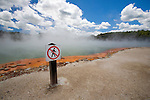 """A """"Do Not Walk"""" danger sign sits next to the boiling and brilliantly coloured Champagne Pool at the geothermal site, Wai-O-Tapu Thermal Wonderland, near Rotorua on the North Island of New Zealand."""