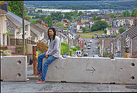 Pictured: Adam Romain whose car and house were vandalised sits on one of the concrete barriers now installed at Waun Wen Road where cars were set alight in Mayhill, Swansea, Wales, UK. Wednesday 16 June 2021<br /> Re: Riot aftermath in the Mayhill area of Swansea, Wales, UK.Pictured: Wednesday 16 June 2021<br /> Re: Riot aftermath in the Mayhill area of Swansea, Wales, UK.