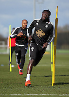 Pictured L-R: Andre Ayew chases Bafetimbi Gomis Thursday 25 February<br /> Re: Swansea City FC training at Fairwood, near Swansea, Wales, UK, ahead of their game against Tottenham Hotspur.
