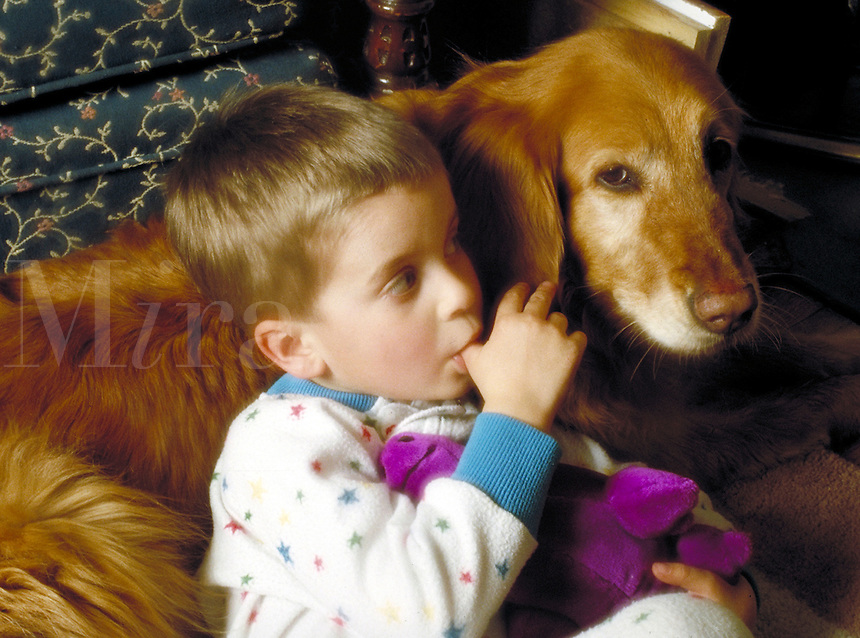 Small boy sucking thumb with dog. Family. Douglaston NY.