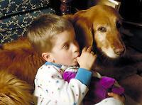 Small boy sucking thumb with dog. Family. Douglaston NY.