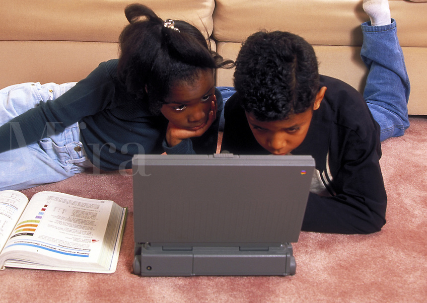 African-American children using laptop computer at home.