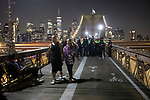 NEW YORK, NY — SEPTEMBER 25, 2020:  A couple walks away from a line of NYPD officers as they close the walkway on the Brooklyn Bridge during a protest against a Kentucky Grand Jury decision to not directly indict the officers involved in the shooting of Breonna Taylor, a 26 year-old EMT who was killed in her Louisville home by police on March 13th of this year, on September 25, 2020 in New York City.  Former police detective Brett Hankison faces three felony charges of wanton endangerment.  Photograph by Michael Nagle