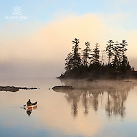 """""""Paddling to Sunrise""""<br /> The canoeist enjoys a sunrise paddle on a cool, foggy morning in the Boundary Waters Canoe Area Wilderness (BWCAW). The wilderness is a treasure with endless beauty."""