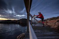 Female runner stretching after an evening run, West Sweden, Sweden - Västsverige, Sverige
