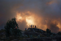 People watch smoke rise into the air at the site of a wildfire in Lousame, near A Coruna, on August 29, 2013. Spain is prone to forest fires in summer because of soaring temperatures, strong winds and dry vegetation. Last year wildfires destroyed some 150,000 hectares of land in Spain from January to July, after one of the driest winters on record. © Pedro ARMESTRE