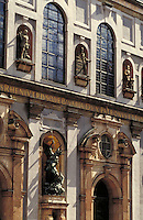 St. Michael's Church facade with statues in niches and large round-arched windows; strong cross light. Munich Bavaria Germany.