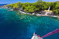 Tourists on a catamaran cruise marvel at the clear waters of Hawai'i Island's Kealakekua Bay. Swimmers and snorkelers enjoy the water near the shore and the Captain Cook Monument.