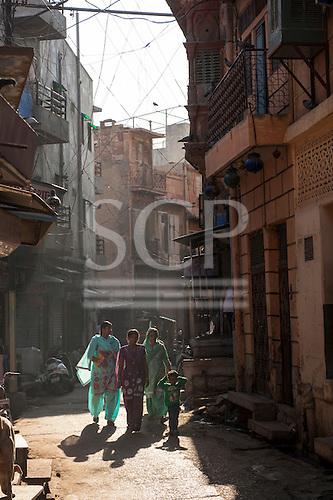 Jodhpur, India. Street scene with three women in saris and a boy.