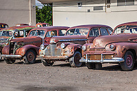 Waiting to be restored, antique cars for sale line a lot on mainstreet in a rural Colorado town.