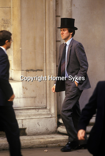 """City of London. 1980's<br /> A Topper from a Discount House they bought and sold discounts and or negotiates bills of exchange or promissory notes. Traditionally they never took notes of their meeting; they were supposed to remember the details. The wearing of top hats was abandoned during the mid to late 1980s.<br /> <br /> <br /> A """"Topper"""" at a Discount House. He carries no brief case or files, a clue that might suggest that he was indeed a Partner or Senior Staff at Discount House, rather than a runner for a stock broker. ( Discount House primarily operated in the UK. They bought and sold discounts and/or negotiates bills of exchange or promissory notes. This is generally performed on a large scale with transactions that also include government bonds and treasury bills.) The """"privileged"""" position of the Discount Houses vis a vis the Bank of England ended in 1996. Traditionally they never took notes of their meetings: they were supposed to remember the details. The wearing of top hats was abandoned during the mid to late 1980s."""