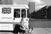 England. Greater Manchester. Salford. Women living in poverty. A young mother pushes a stroller with her young daughter. They both walk on the sidewalk and pass by a food truck parked on the road which sells fish and chips food. A food truck is a large motorized vehicle (such as a van) or trailer, equipped to cook, prepare, serve, and/or sell food.The lorry has a Union Jack flag painted on its side. The national flag of the United Kingdom is the Union Jack, also known as the Union Flag. Salford is a city in the Metropolitan Borough of Salford in Greater Manchester. North West England is one of nine official regions of England. © 1990 Didier Ruef