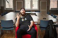 BNPS.co.uk (01202) 558833<br /> Pic: ZacharyCulpin/BNPS<br /> <br /> Pictured: Punk rock Mayor Andy in the Frome Council Chamber<br /> <br /> At 6ft 9in tall, dressed all in black, with a big beard and wearing wayfarer shades, Andy Wrintmore does not look like your typical mayor.<br /> <br /> But the 29-year-old hardcore punk rock drummer is a big hit with old and young constituents in his hometown of Frome, Somerset.<br /> <br /> Andy, a member of punk band SickOnes, was elected to the town council by a landslide vote in 2019 and chosen to become the town's mayor in May this year.<br /> <br /> He has earned the moniker the 'punk rock mayor of Frome' and has even been interviewed by Kerrang magazine about his new career - cutting ribbons and meeting local community groups.