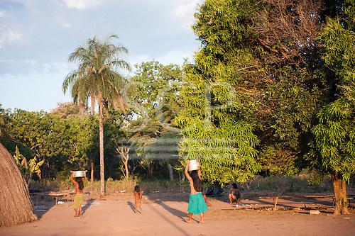 Xingu Indigenous Park, Mato Grosso, Brazil. Aldeia Matipu. Women carry water in aluminium pots on their heads.