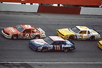 HAMPTON, GA - NOV 3:  Bill Elliott, #9 Ford, Tommy Ellis, #18 Chevrolet, and Geoff Bodine, #5 Chevrolet, race through a turn during the Atlanta Journal 500 NASCAR Winston Cup race at Atlanta Motor Speedway, November 3, 1985. (Photo by Brian Cleary/www.bcpix.com)