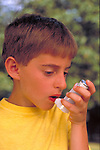 young boy using inhaler for asthma