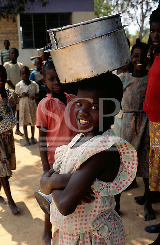 Mbati, Zambia. Smiling young girl in a pink and white top carrying cooking pots on her head; Chambeshi River.