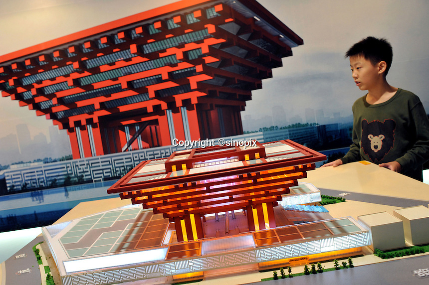 """A kid is looking at a model of China Pavilion at the Shanghai Urban Planning Exposition Center in Shanghai, China. The Chinese Pavilion is designed with the concept of """"Oriental Crown."""" The traditional Chinese wooden structure element, Dougong brackets, is introduced. Its main colour is """"Gugong (Forbidden City) Red"""" which represents the taste and spirit of Chinese culture. The permanent facilities including the World Expo Axis, Chinese Pavilion, Theme Pavilion, Performance Center and Expo Center of the World Expo 2010, will be completed by the end of this year..26 Oct 2009"""