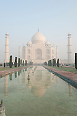 Agra, Utar Pradesh, India. The Taj Mahal seen from the end of the al Hawd al-Kawthar tank, with its reflection, in the early morning mist.