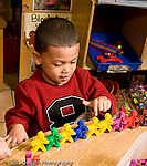 Education Preschool 3-5 year olds boy counting colored plastic connecting people figures square