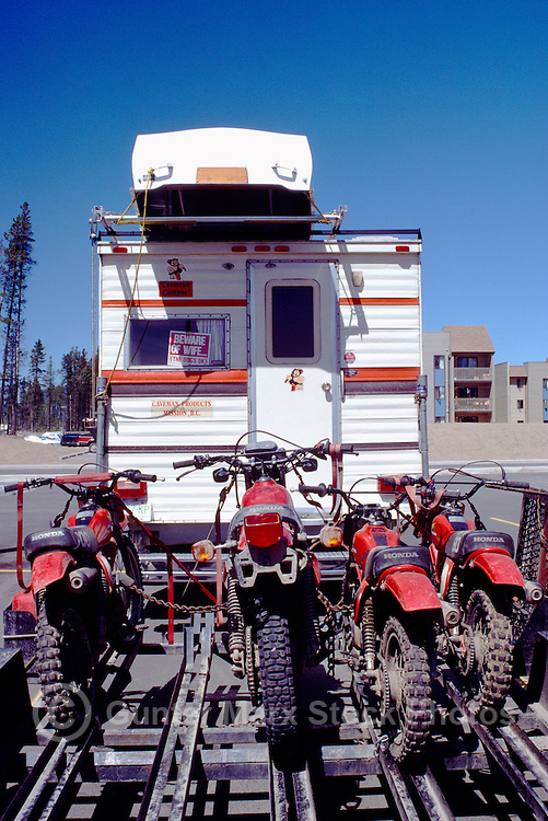 RV Pickup Camper Truck pulling Trailer loaded with Motocross Dirt Bikes and carrying Rowboat on Roof Rack