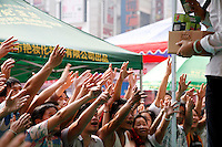 "An audience eagerly grabs for boxes of supposedly ""giveaway"" shampoo, which later turns out to be sales items, at a square in Guangzhou, Guangdong Province, China. .10 Nov 2006"