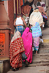 A group of pilgrims with containers of holy water from the Ganges ascend the ancient stone steps from the river banks.