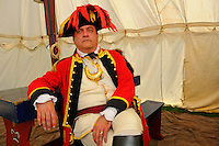 Double-ranked Captain and Lieutenant Colonel of the British First Regiment of Foot Guards, rests in his tent during a Revolutionary War reenactment. Gold gorget, worn around the neck, and red sash indicate he is on active duty.
